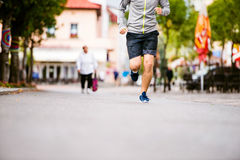 Unrecognizable young man running in town, main street Stock Image