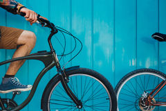 Unrecognizable Young Man Sitting With A Bicycle Along A Blue Wall Background Daily Lifestyle Urban Resting Concept. A young male traveler stands along a blue stock images