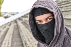 Unrecognizable young man wearing black balaclava sitting on old Royalty Free Stock Image