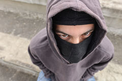 Unrecognizable young man wearing black balaclava sitting on old. Unrecognizable young man wearing black balaclava sitting on stairs, looking at the camera Stock Photos