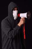 Unrecognizable young man wearing white balaclava, black hoodie a. Nd holding a megaphone in his hand ready to protest at a rally on a dark background Stock Photo