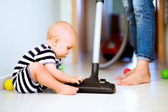 Young mother with a baby boy doing housework. Royalty Free Stock Image