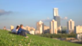 Unrecognizable young people sitting on the grass in city park against urbanscape. 4K bokeh background shot. Unrecognizable young people in city park against stock video footage
