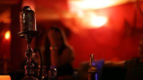 Unrecognizable young people smoking Shisha water pipe in a bar stock footage