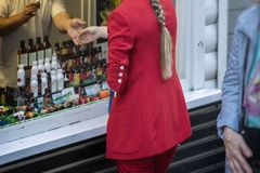Unrecognizable young woman, back to us, in red suit makes the choice in the shop, trade store of natural cosmetics royalty free stock photo