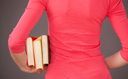 Unrecognizable young woman holding three books Royalty Free Stock Photo