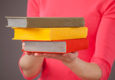 Unrecognizable young woman holding three books Royalty Free Stock Image