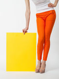 Unrecognizable young woman. In orange pants holding blank yellow paper, closeup shot Royalty Free Stock Photos