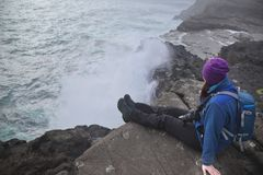 Unrecognizable young woman sitting on the cliff of the Island Vágar of the Faroe Islands