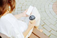 Woman resting with coffee and smartphone. royalty free stock photos