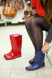 Unrecognizable young woman trying blue waterboots in hand Stock Photography