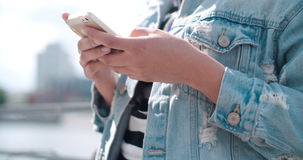 Unrecognizable young woman wearing denim jacket typing on phone during sunny day. Stock Photo