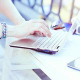 Young woman using laptop and typing outdoor. Unrecognizable young woman working on laptop and typing on the keyboard outdoors Royalty Free Stock Photography