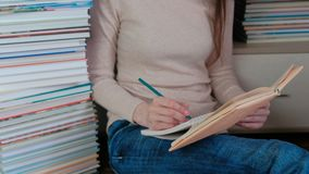 Unrecognizable young woman writes the notes sitting on the floor among the books.  stock video footage