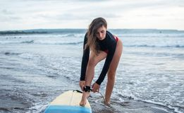Unrecognizble barefoot woman has fixed legrope, stands on sand near surfboard, protects herself from crashing into shore lines,. Has active lifestyle, enjoys stock photography