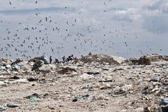 Unrecognizble folk på nedgrävning av sopor Arkivbild