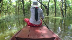 Unrecognized Asian Woman Rows a Boat Through Flooded Mangrove Tree Fores. Tonle Sap Lake, Cambodia. HD Gopro Action stock video
