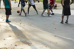 Unrecognized basketball players engaging in a game on an outdoor court in a park with leaves scattered about, shallow focus. Royalty Free Stock Photos