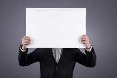 Unrecognized businessman holding a blank sign. Businessman holding a blank sign shot in studio Royalty Free Stock Photos