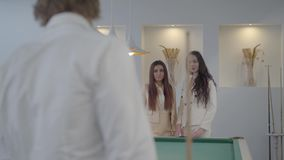 Unrecognized businessman spends leisure playing billiards with two girls. A young man holds a billiard cue while. Bearded successful businessman spends leisure stock video