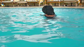 Unrecognized Caucasian senior elderly woman in black hat swims in blue water pool in hotel. Against the backdrop of stock video footage