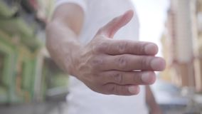 Unrecognized confident middle eastern man extends his strong arm for a handshake close-up. Modern cityscape in the. Background stock footage