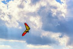 Unrecognized hangglider pilot flies o. Unrecognized brave extreme hangglider pilot flies on a hang glider with deep blue sky and clouds above Stock Photos