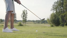 Unrecognized man playing golf on the golf field. Confident man warming up and hitting the ball using a golf club. The. Unrecognized man playing golf on the golf stock video