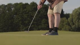 Unrecognized man playing golf hitting golf ball on the golf course. Summer leisure. Slow motion. Unrecognized man playing golf on the golf course. Summer leisure stock video footage