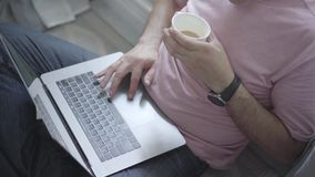 An unrecognized man is sitting by the window and typing on a laptop while drinking coffee. Healthy weekend activities. An unrecognized man is sitting by the stock video