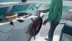 The unrecognized master manages the yacht with the help of a retro steering wheel and control levers. The concept of. Business or life management, vacation or stock footage