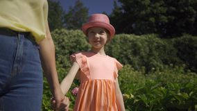 Unrecognized mother walking with small adorable daughter in the summer garden holding hands. Happy family. Woman and stock video footage