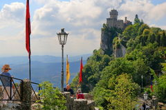 Unrecognized people and Cesta castle tower in San-Marino, Italy. San Marino, Italy - August 16, 2015: Unrecognized people walk along stone road to Cesta castle Royalty Free Stock Images
