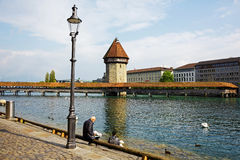 Unrecognized people by the river Reuss. LUCERNE, SWITZERLAND - MAY 02, 2016: Unrecognized people are sitting on the banks of the river Reuss. They can see a Royalty Free Stock Images