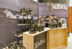 Whisky Dram Festival in Kiev, Ukraine. Unrecognized presenters work on Ardbeg Single Malt peated Scotch Whisky distillery booth at 3rd Ukrainian Whisky Dram stock image