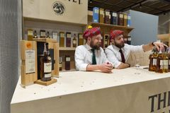 Whisky Dram Festival in Kiev, Ukraine. Unrecognized presenters works on Glenlivet Single Malt Scotch Whisky Highland distillery booth at 3rd Ukrainian Whisky royalty free stock photos