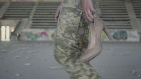 Unrecognized woman in military uniform walking slowly in dusty dirty abandoned building carrying high-heeled shoes in. Hands. The concept of a strong and stock video footage