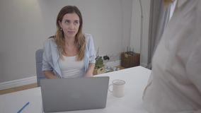 Unrecognized woman scolding young pretty Caucasian girl sitting at the table with laptop. New female employee stock video
