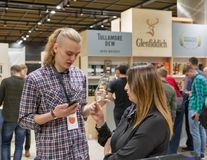 Whisky Dram Festival in Kiev, Ukraine. Unrecognized young people tasting Single Malt Scotch Whisky at 3rd Ukrainian Whisky Dram Festival in Parkovy Exhibition Royalty Free Stock Image