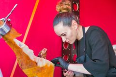 Kyiv Wine Festival by Good Wine in Ukraine. Unrecognized young woman chef carefully cuts the pork leg jamon thin slices at Kyiv Wine Festival outdoor food court Stock Image