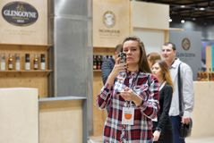 Whisky Dram Festival in Kiev, Ukraine. Unrecognized young woman make smartphone photos of whisky glass at 3rd Ukrainian Whisky Dram Festival in Parkovy Stock Images