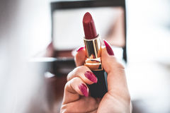 Unrecognized Young women doing make-up going for date. Red lipstick. In his hand and red nails Stock Images