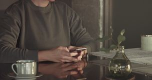 Unrecognizible woman texting using smartphone, then call and drinks tea stock video footage