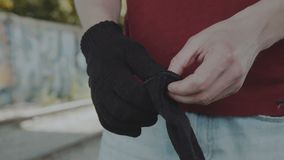 Unrecogrizable man puts on black material gloves. Close-up. 4K. Unrecogrizable man puts on hand black material gloves. Close-up. 4K stock footage