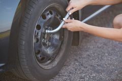 Unrecongnizable professional female mechanic going to change car wheel, uses special equipment, has damage with something. Cropped stock images