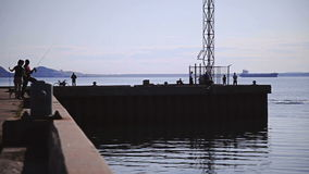 Unreconizable People Fishing Mackerel on a Pier. Unreconizable People Fishing Mackerel on a Dock stock video footage