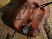 Unrefined crude oil is collected in a jerry can at a heavily polluted, illegal oil field Stock Photo