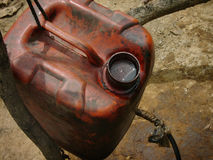 Unrefined crude oil is collected in a jerry can at a heavily polluted, illegal oil field Royalty Free Stock Image