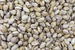 Unrefined pistachios in shell on market counter in daylight. stock images