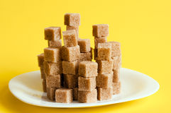 Unrefined sugar on a yellow background Royalty Free Stock Image